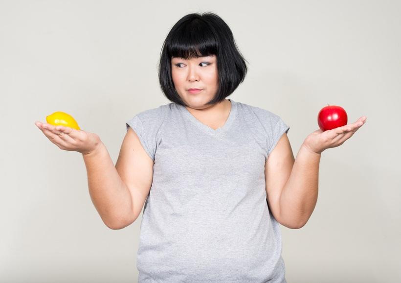 Asiatin, die Zitrone Apple hält