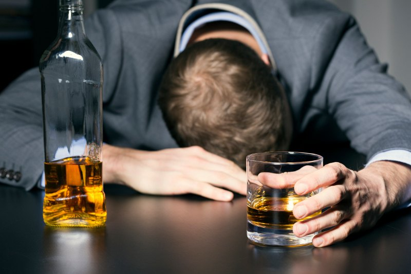 The 7 best hangover cures backed by science man with alcohol in hand and resting head on table the easiest way to ccuart Images